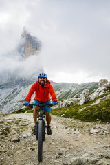 View of cyclist riding mountain bike on trail in Dolomites,Tre Cime di Laverado in background, South Tirol, Italy