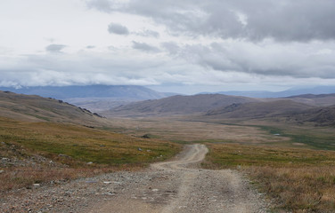 Extreme rocky road path down to a mountain valley from the pass in cloudy dark weather with rain and fog Plateau Ukok Altai Siberia Russia