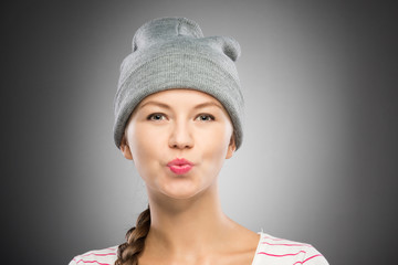 Attractive young woman in winter hat sending a kiss