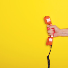 Woman hand holding retro orange phone tube against yellow background