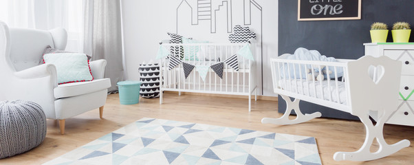 New child bedroom with armchair, cot, cradle, chalkboard, carpet and floor panels, panorama