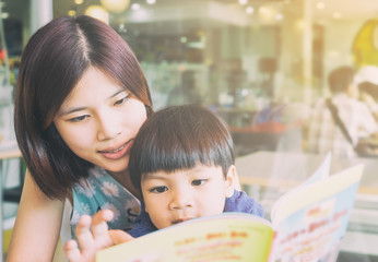 Asian mother is reading her son an educational fun book.