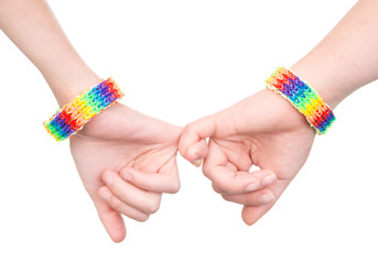 two woman's hands with a bracelet patterned as the rainbow flag together. isolated on white