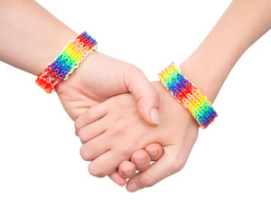 woman's hands with a bracelet patterned as the rainbow flag. isolated on white