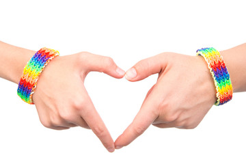 Female hands with a bracelet patterned as the rainbow flag showing heart sign. idolated on white