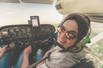 Confident female pilot with headset smiling in the private helicopter. Smiling happy woman wearing headphones and enjoying the flight on a private jet. Fototapete