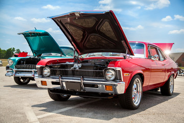 Fototapeta Two old American 70s customized muscle cars with the hoods open on the show obraz