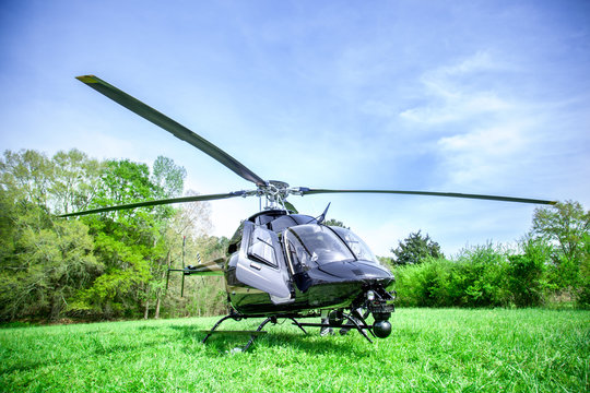 Black with gray stripes helicopter standing on green grass field getting ready to fly over blue sky.