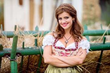 Beautiful woman in traditional bavarian dress against hay wagon