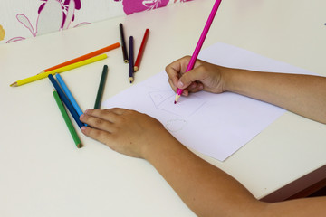 The child draws crayons house on a bright sheet of paper.