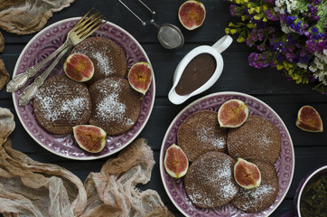 Chocolate pancakes with chocolate sauce and figs
