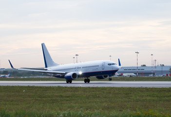 white and blue passenger plane is landing away from airport