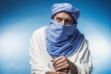 Berber man wearing blue turban with white robe. Leaning on cane.