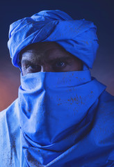 Berber man in night light wearing blue turban with white robe. S