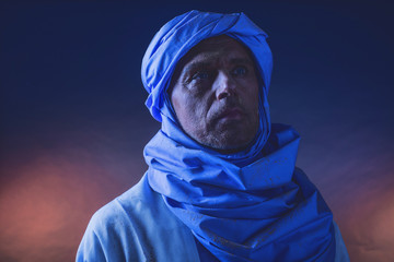 Berber man in night light wearing blue turban with white robe. S