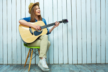 Young woman play on guitar and sings.