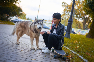 Young asian girl feed the dog in the park. Happy human sit on the longboard or skateboard outdoor near home animal.