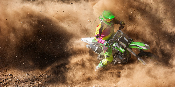 Motocross rider racing in a large cloud of dust and debris