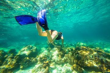 Young female snorkeling in tropical sea. Woman apnea swims in coral reef.