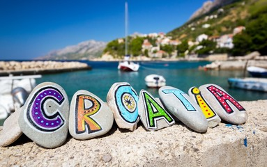 Croatia country name painted on the stones, boat in background