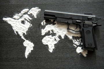 black automatic gun over the world formed with the powder of heroin