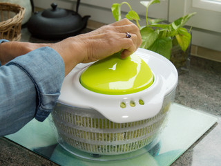 hand of a woman spinning salad in the kitchen