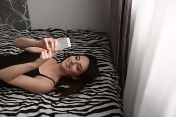 Yong brunette girl lying in the bed taking selfie