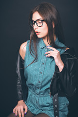 Beautiful young girl. Glasses, denim overalls, a black leather jacket. Sexy girl. Trendy toning image.