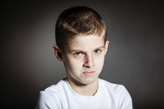 Angry male child posing pensively in dark room