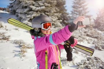 Happy woman taking selfie on winter mountain