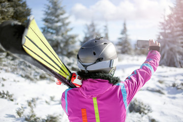 Happy woman taking selfie on winter mountain