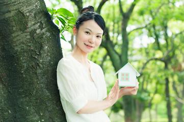 家の模型を持つ女性