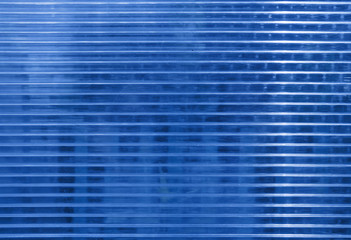 Blue polycarbonate surface with objects behind