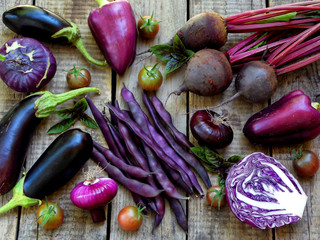 purple vegetables on wooden background - eggplant, cauliflower, green beans, cherry tomatoes, basil, onion, cabbage, sweet pepper