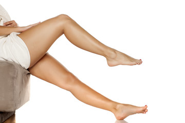 young women applied body cream on her legs
