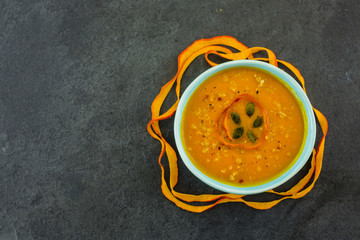 Tasty pumpkin soup in bowl on dark stone background with space for text. Top view.