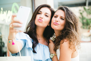 Beautiful young women taking a selfie in the street.