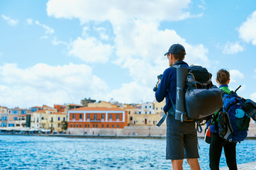couple tourists walking on the waterfront of Chania bay backround, Crete, Greece