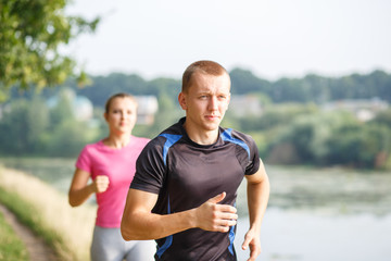 Young athletic people jogging outdoor near pond