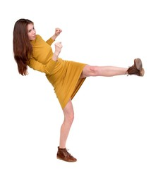 skinny woman funny fights waving his arms and legs. Long-haired brunette in a mustard-colored falls.