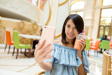 Woman taking photo with fruit juice