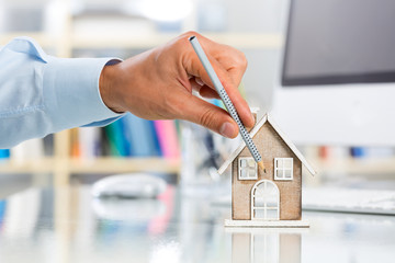 Hand Pointing at House Miniature in Office