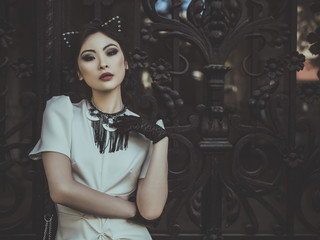 Black-haired asian woman in cat's ears posing on black gates