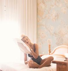 Pretty blonde woman folded head on levitating pillow