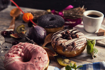 fresh donut with coffee on wooden table with napkin, spoon and f