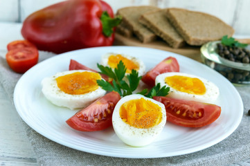 Boiled egg and fresh tomato, black bread - light diet breakfast. Close up