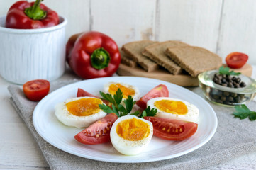 Boiled egg and fresh tomato, black bread - light diet breakfast.