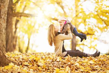 Mutter mit Tochter in den Herbstblättern