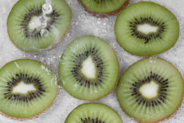 Pour water into sliced kiwis with bubble in water. Selective focus
