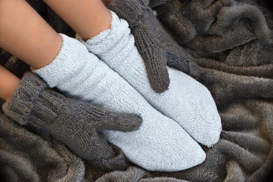 Feet in comfortable and warm woolen socks on a blanket